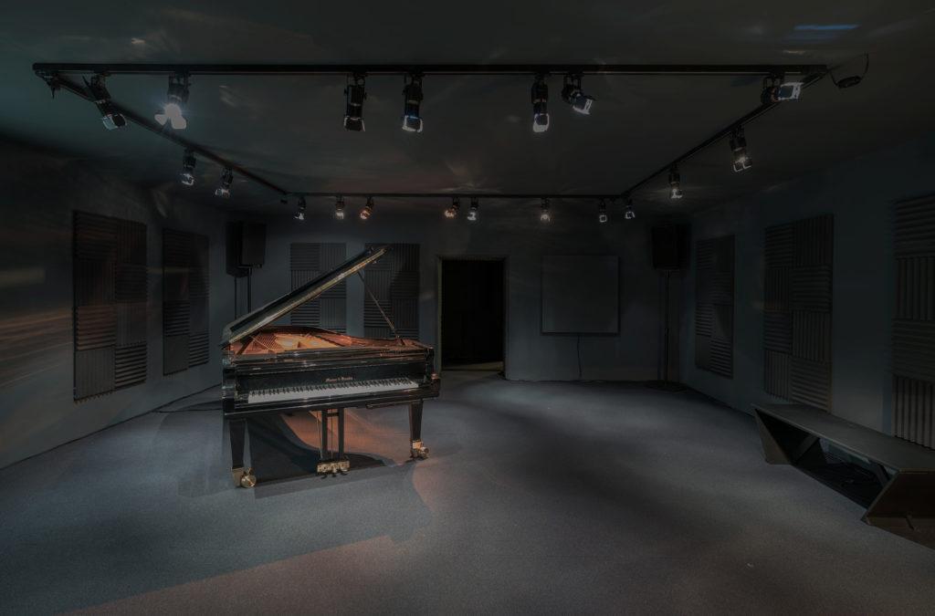 Rana Hamadeh presenteert in een pikzwarte ruimte haar operaproject, en laat deze vergezeld gaan van indringende muzikale klanken.
