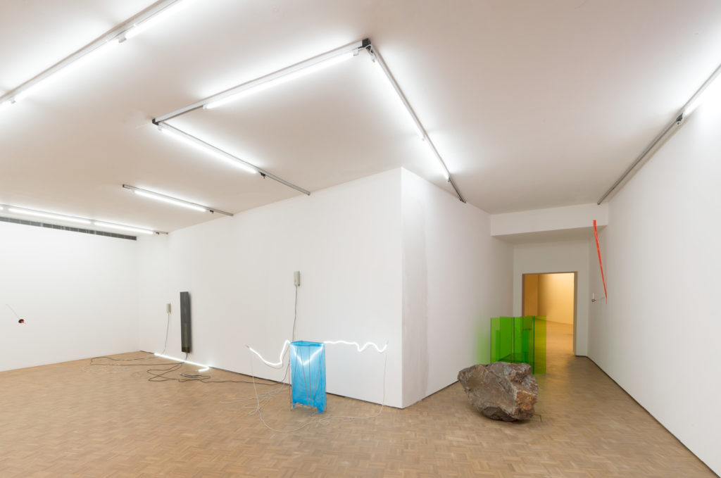 De installatie van Noor van Imhoff begint in de paars verlichte personenlift die sterk contrasteert met de felgroene expositiezaal.